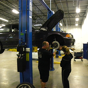 Employees at auto repair shop Coho inspecting a car