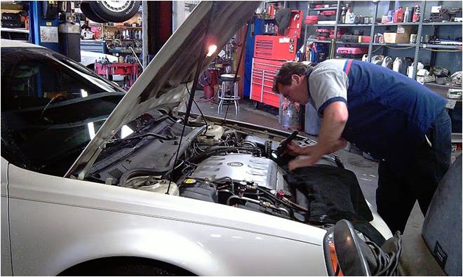 Technician working under the hood of a car