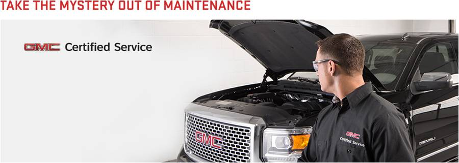 Technician looking at black GMC truck with hood up. The words 'Take the mystery out of maintenance' are apparent